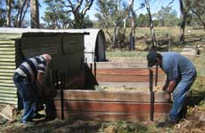 Carl and Athol building a composting heap enclosure at Wilpena.